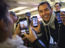 Michele Mattana of Sardinia, Italy, poses with an iPhone 6 Plus and an iPhone 6 on the first day of sales at the Fifth Avenue store in Manhattan, New York September 19, 2014.  REUTERS/Adrees Latif  (UNITED STATES - Tags: BUSINESS TELECOMS)